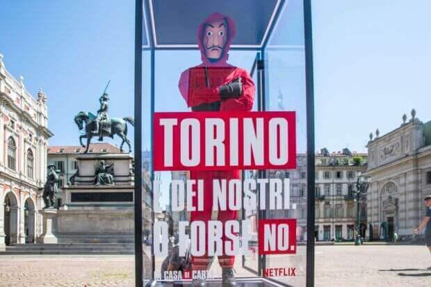 """La casa di carta: Manichino in tuta rossa con maschera di Dalì e scritta: """"Torino è dei nostri?"""""""