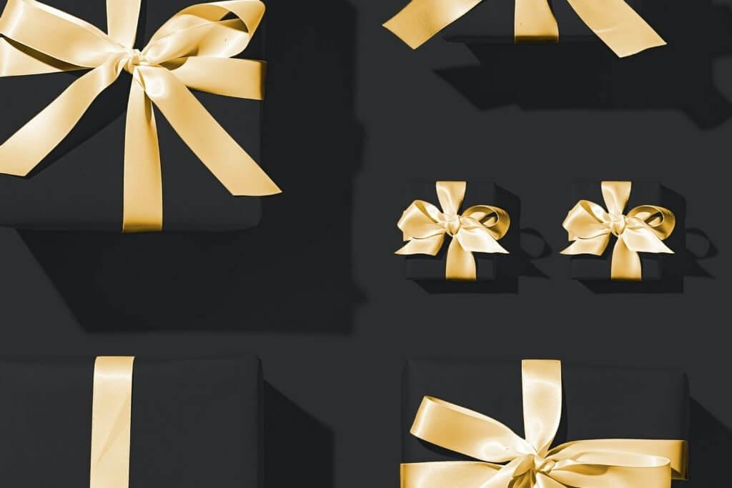 Sfondo nero con regali fiocco oro. Gadget.